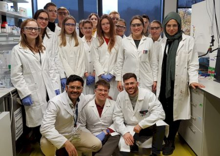 A group of young interested students in lab coats and lab specs research in one of the laboratories of the professorship WW7. They are all dressed in white lab coats and lab specs.